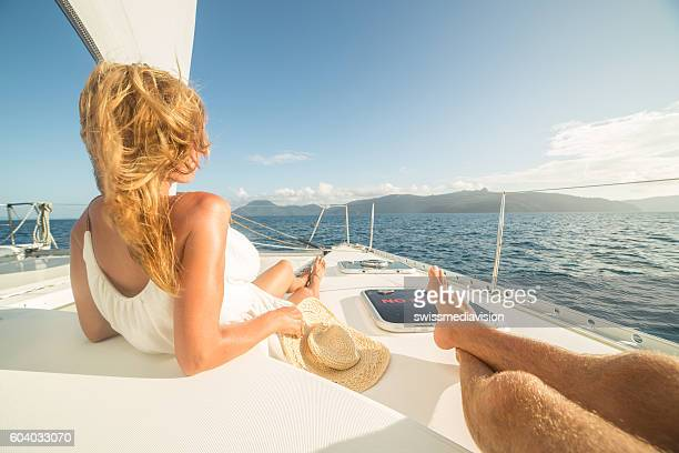 young couple relaxing on sailing boat - catamaran stock photos and pictures