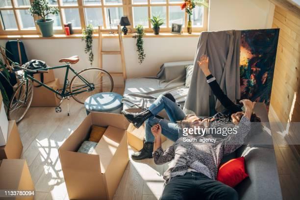 若いカップルは、新しいアパートでソファの上でリラックス - 賃貸借 ストックフォトと画像