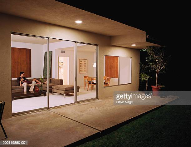 Young couple relaxing on sofa, view sliding glass doors, night
