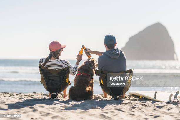 a young couple relaxing on the beach with their dog - oregon coast stock pictures, royalty-free photos & images