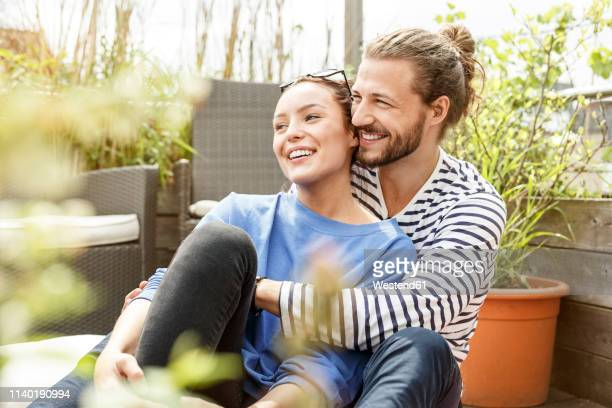 young couple relaxing on their balcony,  embracing - fröhlich stock-fotos und bilder