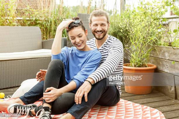 young couple relaxing on their balcony,  embracing - heterosexual couple stock pictures, royalty-free photos & images