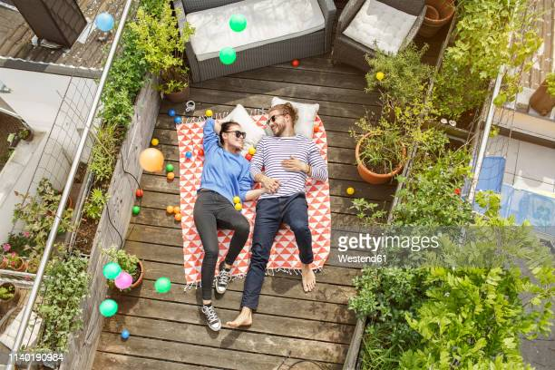 young couple relaxing on their balcony, lying on blanket with arms around - balcony stock pictures, royalty-free photos & images