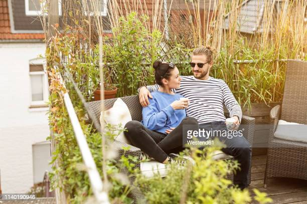 young couple relaxing on their balcony, sitting on couch - balkon stock-fotos und bilder