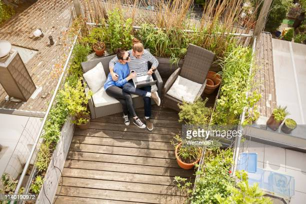 young couple relaxing on their balcony, sitting on couch, using laptop - balcony stock pictures, royalty-free photos & images