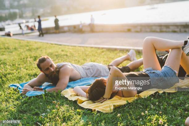 young couple relaxing on waterfront grass, lake como, lombardy, italy - lombardy stock pictures, royalty-free photos & images