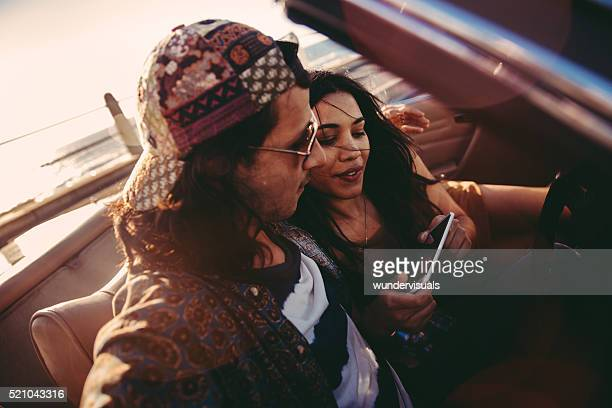 Young couple relaxing with smartphone on a convertible