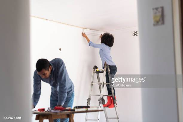 young couple renovating home together fitting new cornice - architectural cornice stock photos and pictures