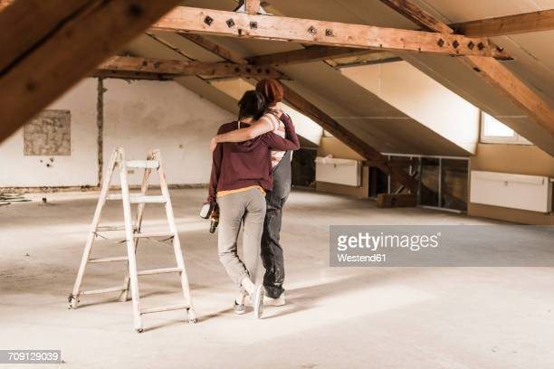 Young couple renovating their new home, looking at construction site