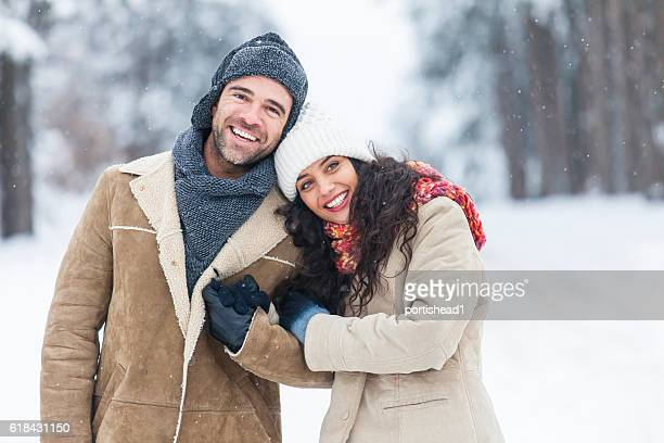 Young couple resting and embracing in snow forest