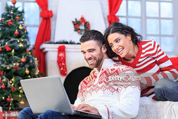 Young couple resting at home and using laptop