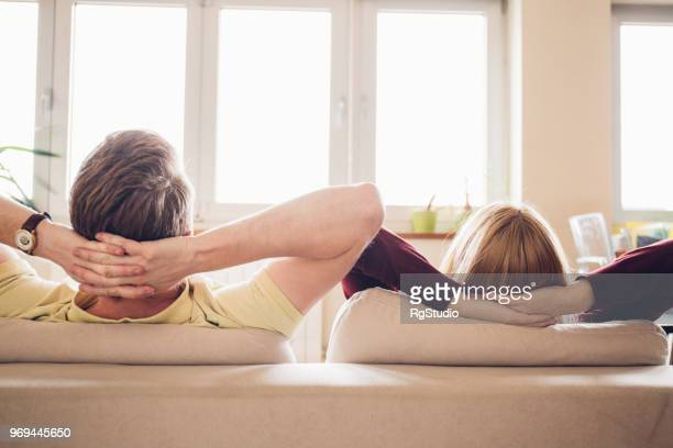 young couple resting at home - hands behind head stock pictures, royalty-free photos & images