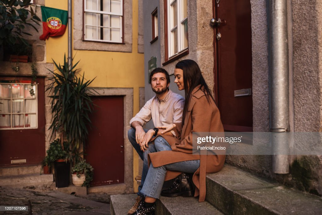 Young couple resting in a city street of Porto, Portugal : Stock Photo