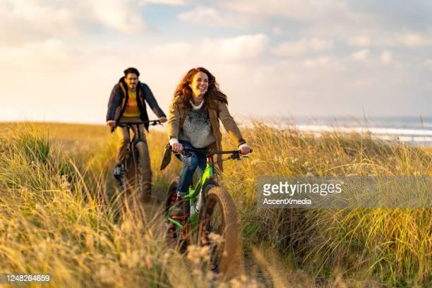 de jonge paar rit vette fietsen op kustspoor - volgen activiteit stockfoto's en -beelden