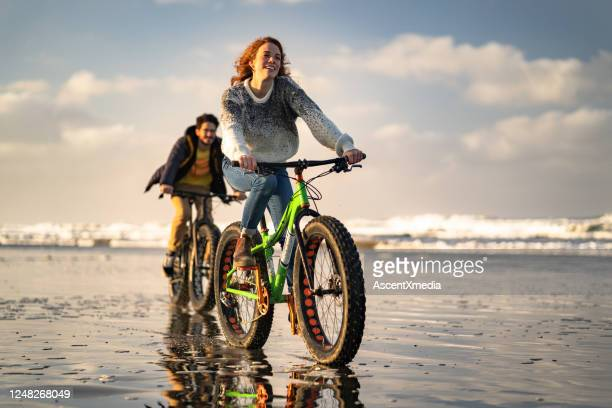 young couple ride fat bikes on the beach, tidal flat - awe stock pictures, royalty-free photos & images