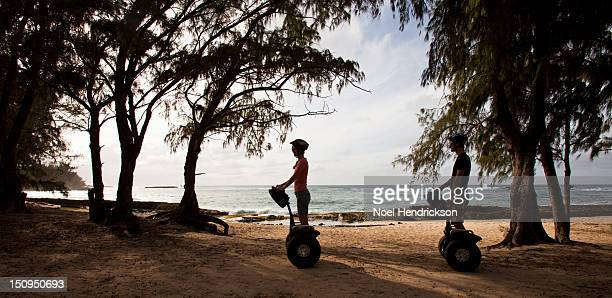 A young couple rides segways together by the ocean