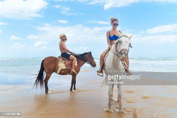 young couple riding a horse on the beach - topless bikini models stock pictures, royalty-free photos & images