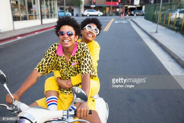 young couple riding a scooter - afro amerikaanse etniciteit stockfoto's en -beelden