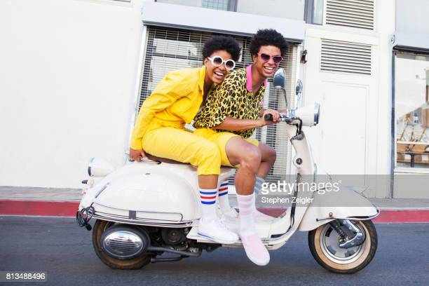 young couple riding a scooter - design stock pictures, royalty-free photos & images