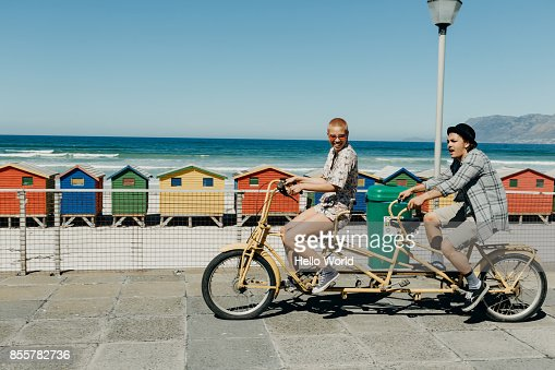 Young couple riding a tandem bicycle on a boardwalk