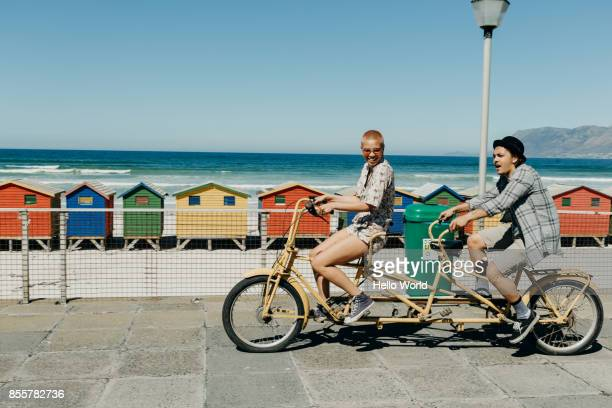 young couple riding a tandem bicycle on a boardwalk - heterosexual couple photos - fotografias e filmes do acervo
