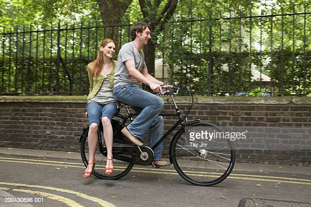 Young couple riding bicycle along street, smiling, side view of man