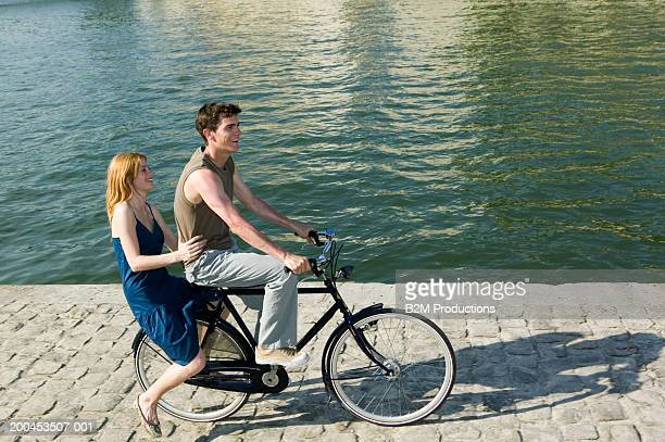 Young couple riding bicycle in quay, woman balancing on back
