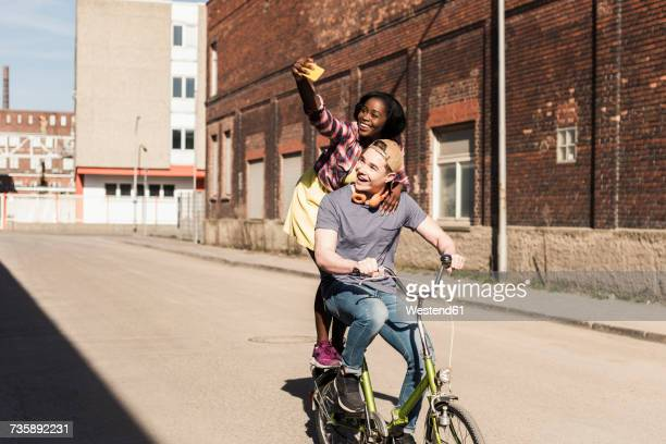 young couple riding bicycle in the street, woman standing on rack, taking selfies - libre de droit photos et images de collection