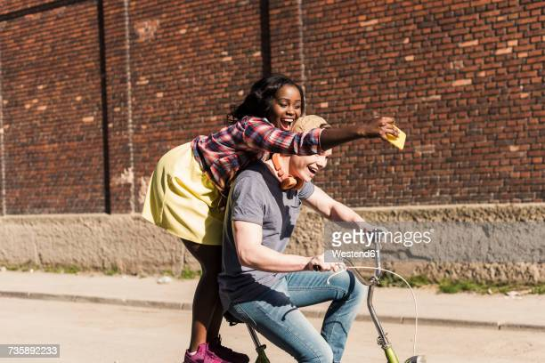 young couple riding bicycle in the street, woman standing on rack, taking selfies - velo humour photos et images de collection
