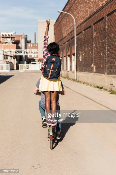 Young couple riding bicycle with girl standing on rack