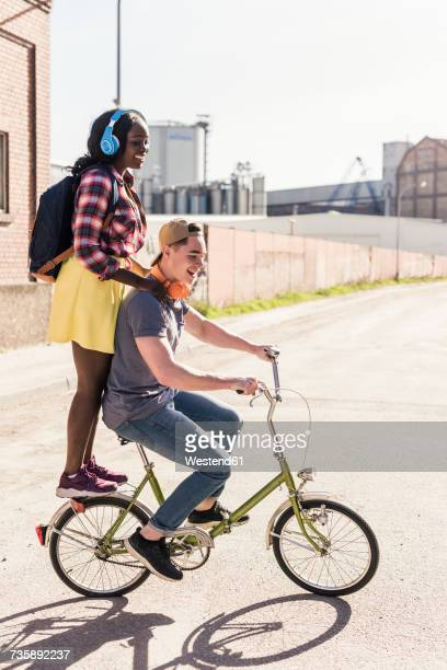 young couple riding bicycle with girl standing on rack - velo humour photos et images de collection