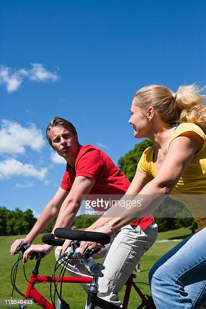 Young couple riding bikes in park