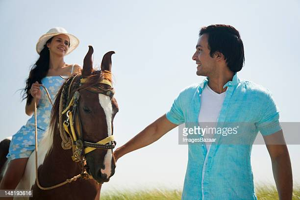 Young couple riding horse on meadow