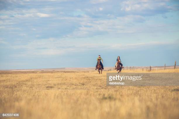 Young Couple Riding Horseback On Montana Prairie