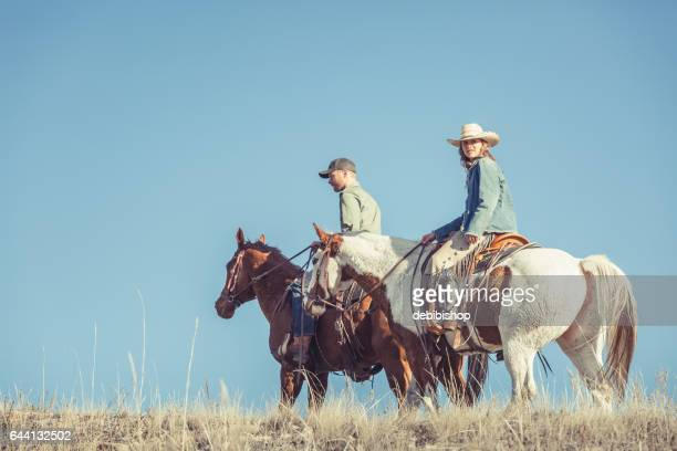 young couple riding horseback - istock stock pictures, royalty-free photos & images