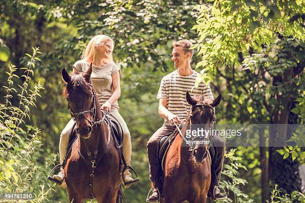 Young couple riding horses in nature and communicating.
