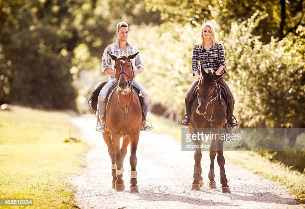 Young couple riding horses in nature.