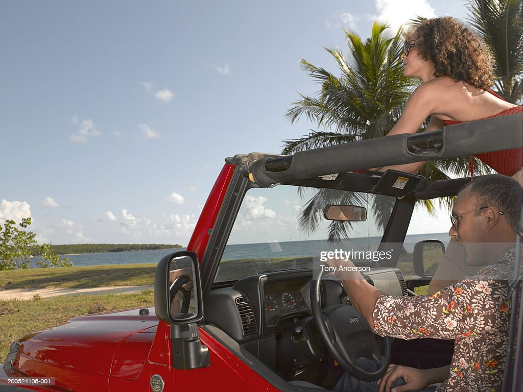 Young couple riding in SUV with open top in tropical setting. : Stock Photo