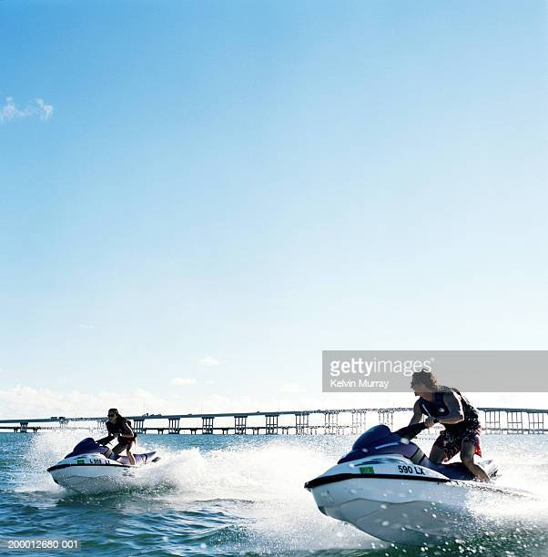 young couple riding jet boats - jet ski stock pictures, royalty-free photos & images