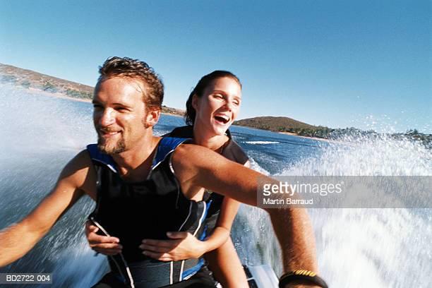 Young couple riding jet ski, smiling, close-up