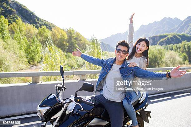 Young couple riding motorcycle together