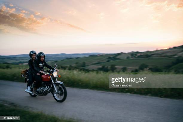 young couple riding on motorcycle at country road during sunset - montar imagens e fotografias de stock