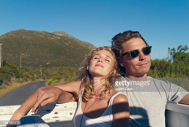 Young couple riding on the back of a pickup