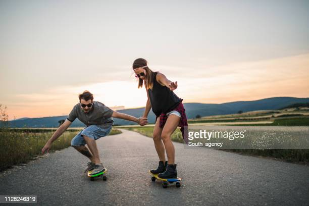 young couple riding skateboards together - longboard skating stock pictures, royalty-free photos & images