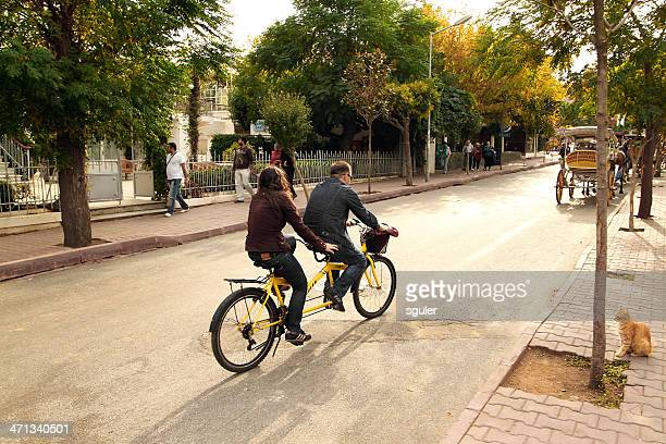 young couple riding tandem bicycle