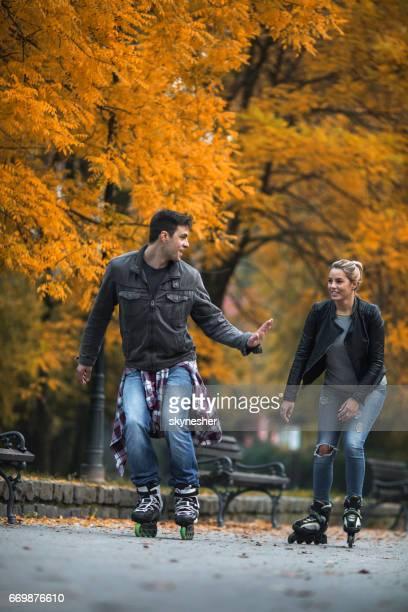 Jeune couple Rollers dans le parc pendant la saison d'automne.