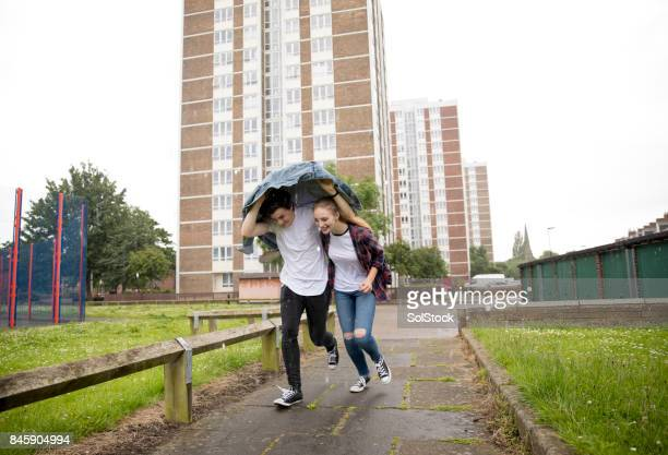 Young Couple Run In The Rain