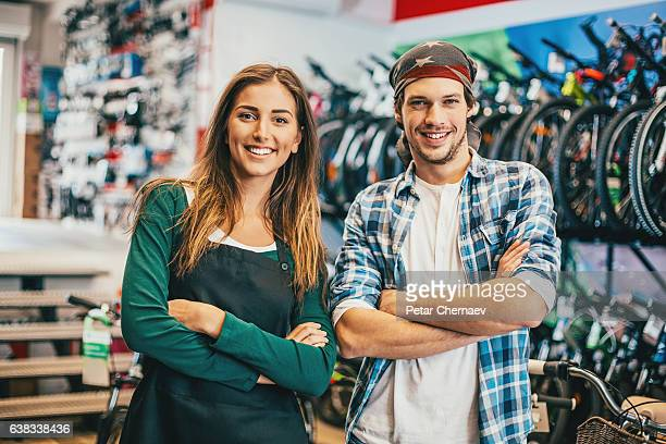 Young couple running a bike shop
