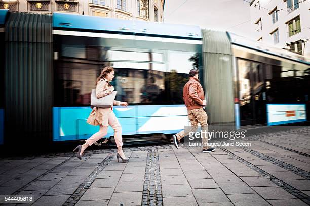 Young couple running after cable car, Munich, Bavaria, Germany