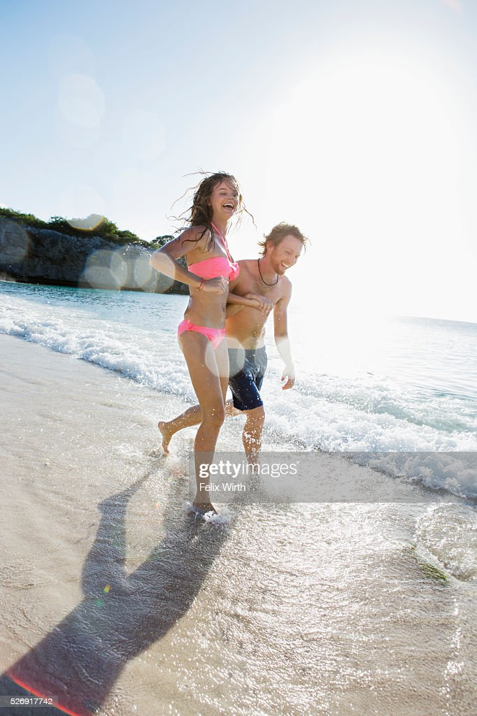 Young couple running along sandy beach : Stockfoto